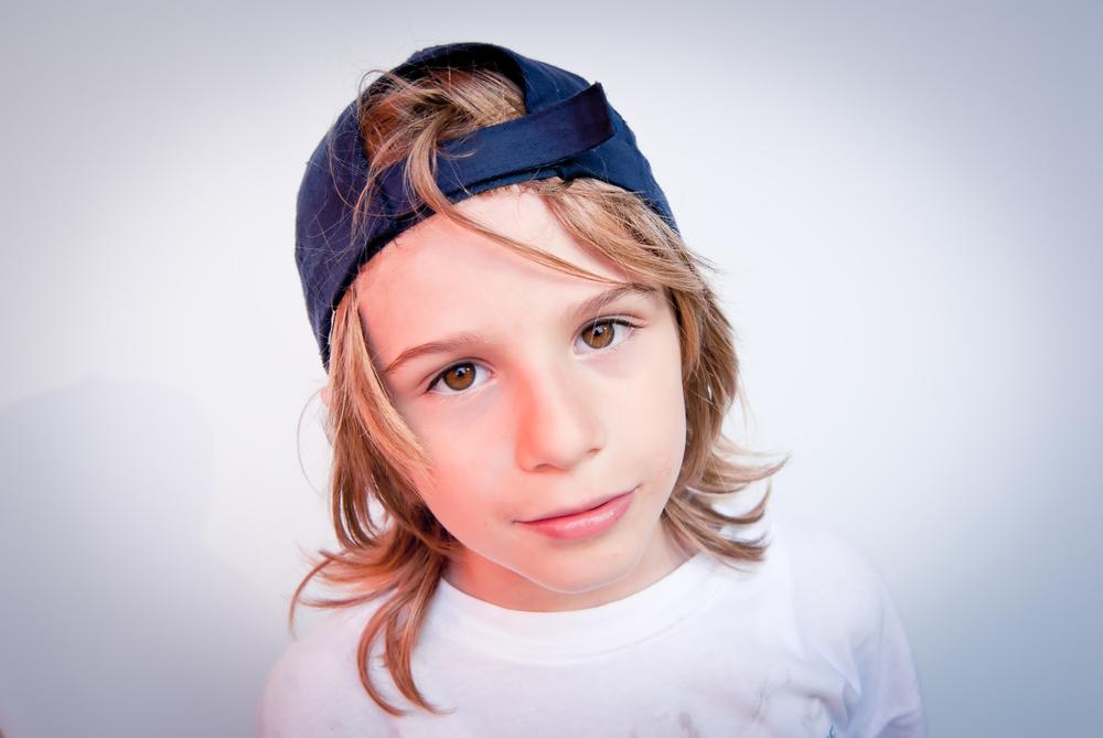 Chłopiec z włosami do ramion w czapce