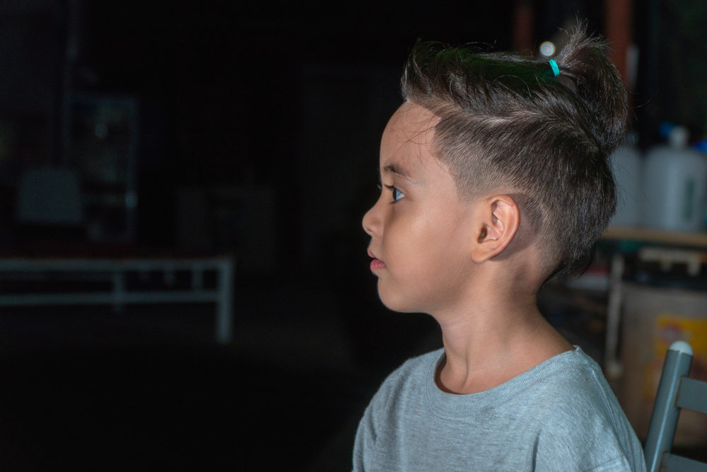 Chłopiec z włosami do ramion w kucyku