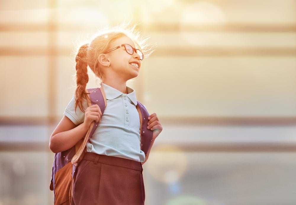 Dziewczynka z warkoczem idzie do szkoły