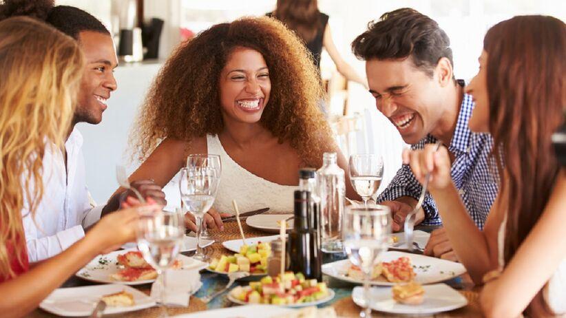 Roześmiani ludzie przy jedzeniu