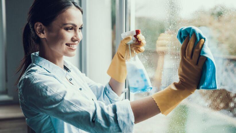 Młoda kobieta myje okna.