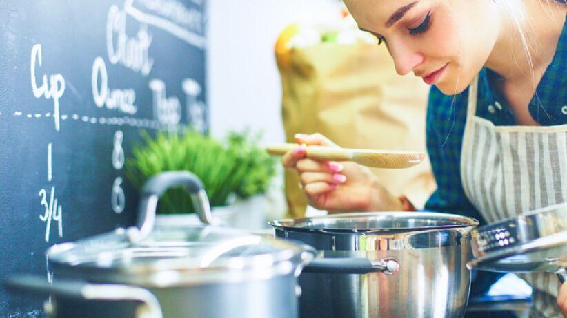 Młoda kobieta gotuje obiad.