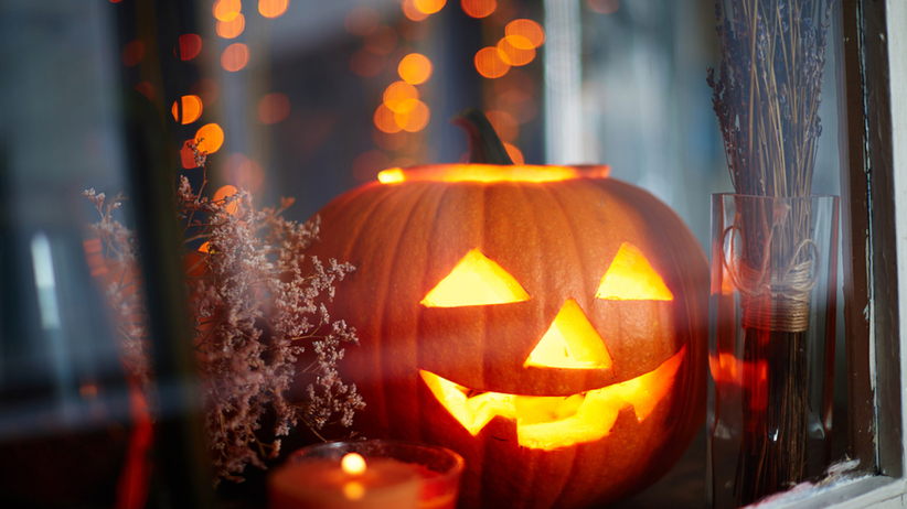 Lampion z dyni stoi w oknie jesienią na Halloween