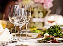 Na eleganckim stole stoją szklane kieliszki i talerze z jedzeniem.