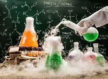 Na szkolnej ławce chemik przeprowadza doświadczenie. W tle widać tablicę.