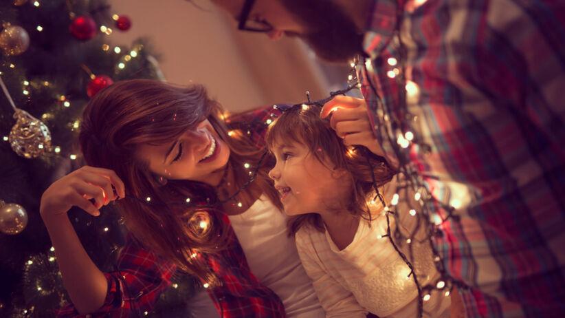 Rodzina wiesza lampki świąteczne na choince