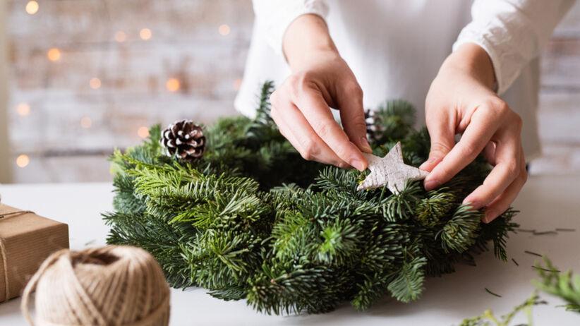 Kobieta przygotowuje wieniec adwentowy do udekorowania domu na święta Bożego Narodzenia