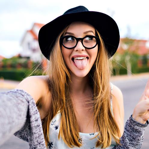 Uśmiechnięta dziewczyna w kapeluszu i okularach pokazuje język