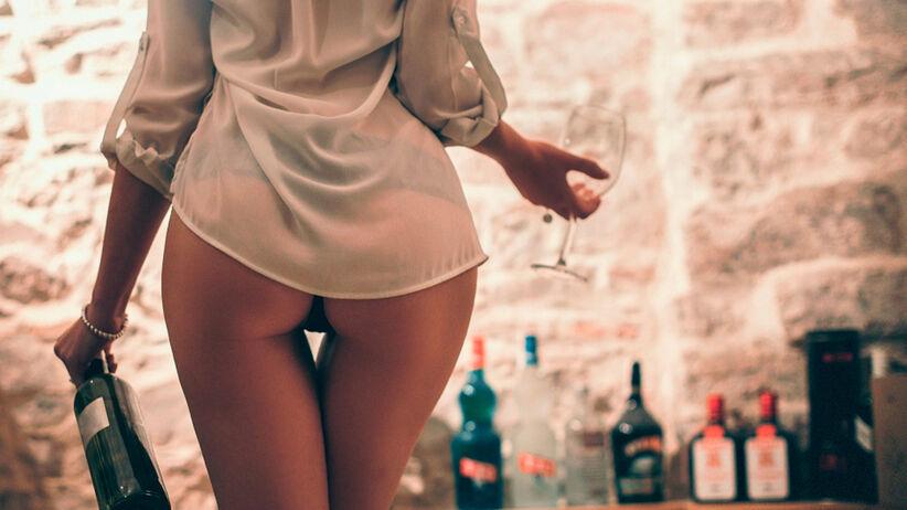 Seksowna kobieta w samej koszuli z winem