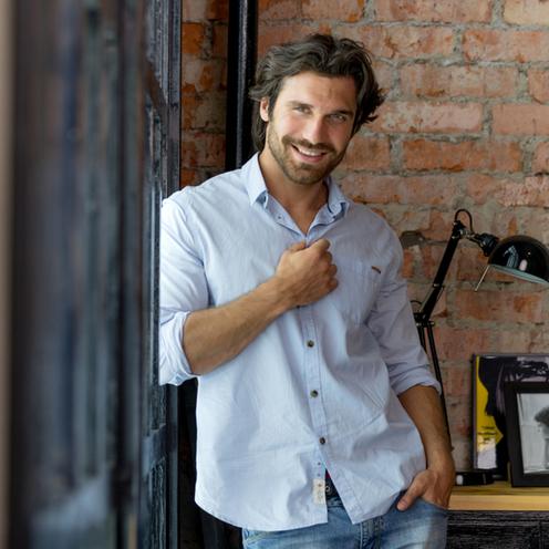 Mężczyzna uśmiechnięty stoi przy ścianie.