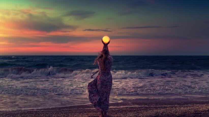 Młoda dziewczyna na plaży trzyma Księżyc w rękach