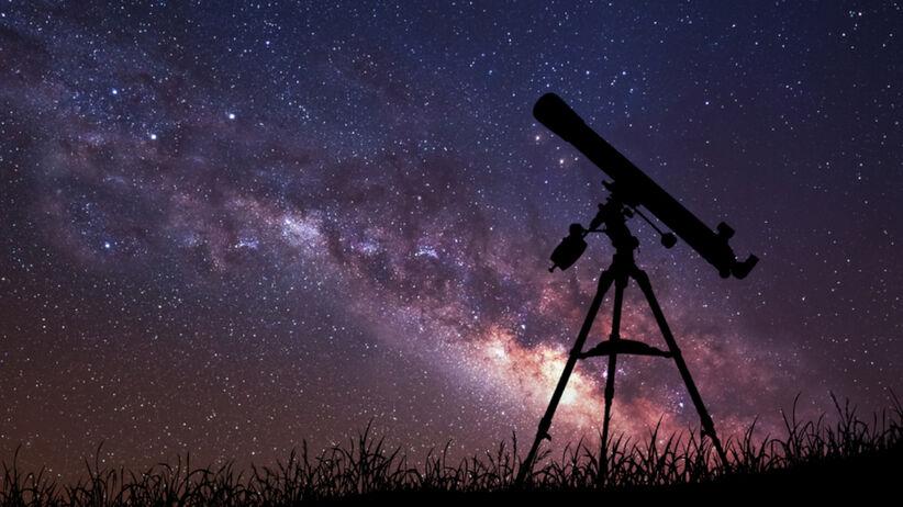 Teleskop stoi na górce na tle gwieździstego nieba