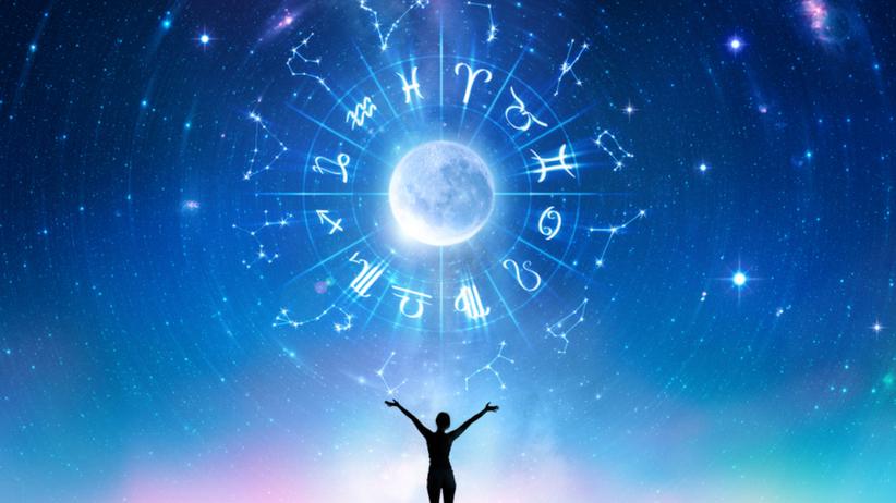 Człowiek w nocy pod gwiazdami, na niebie rozrysowany horoskop