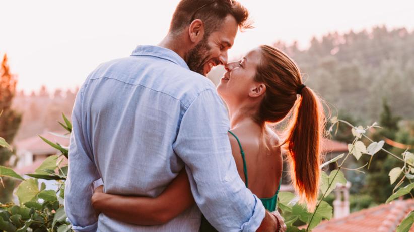 Para uśmiechnięta całuje się przy zachodzie słońca