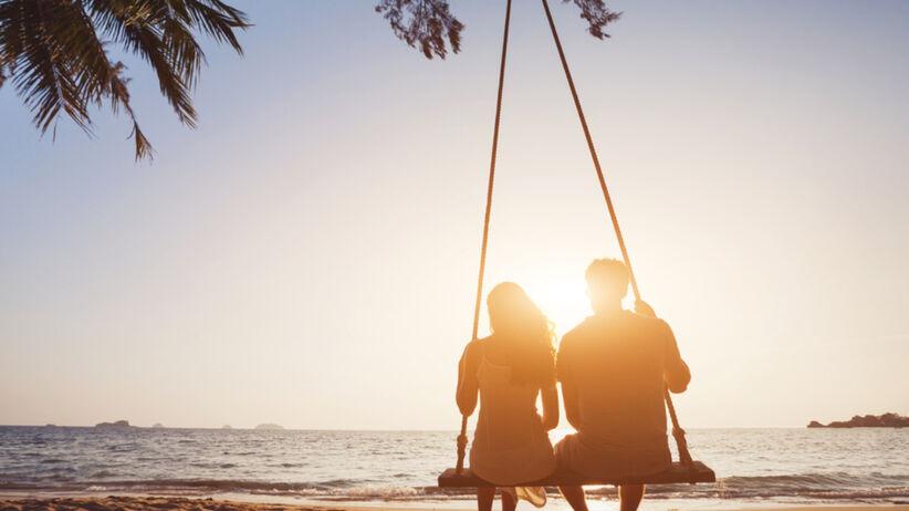 Dwójka zakochanych ludzi siedzi na plaży na huśtawce i wpatruje się w ocean