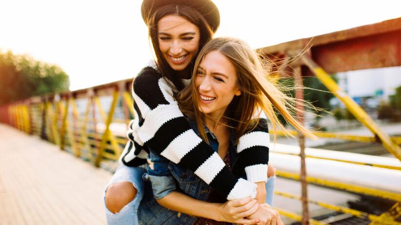 Dwie siostry przytulone ze sobą, jedna ma na sobie kapelusz, a druga trzyma ją na plecach