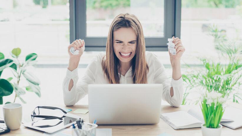 Kobieta denerwuje się w pracy siedząc przy laptopie