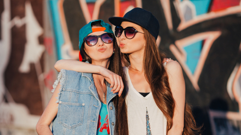 Dwie luźno ubrane przyjaciółki w kaszkietówkach i okularach przeciwsłonecznych na tle graffiti