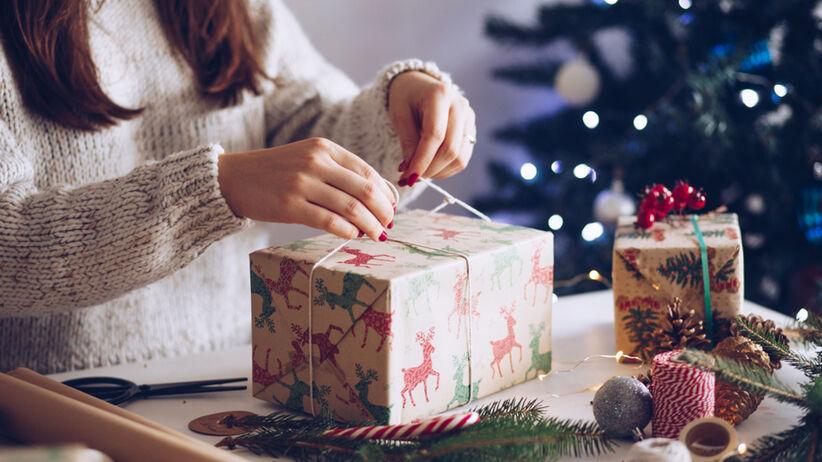 Dziewczyna w swetrze z czerwonymi paznokciami pakuje prezent na święta