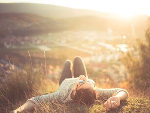 Szczęśliwa kobieta leży na łące. W tel widać zachód słońca.