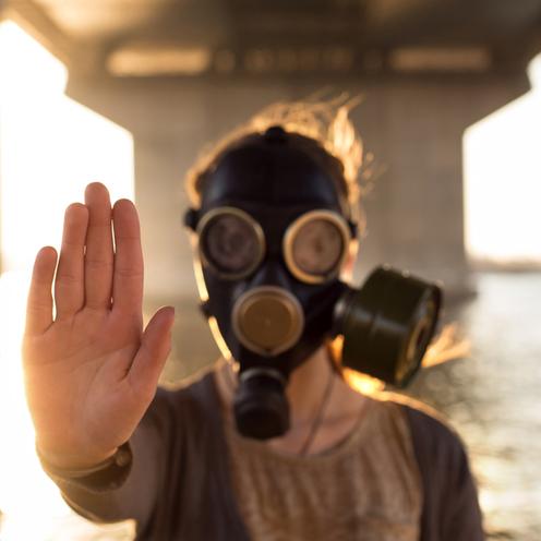 Człowiek w masce przeciwgazowej z wyciągniętą do przodu ręką
