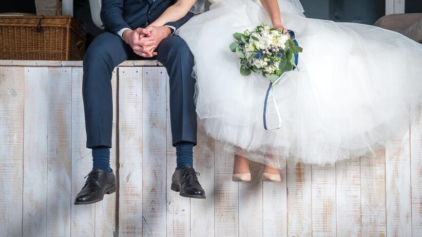 Para młoda siedzi na drewnianym podeście w dniu ślubu