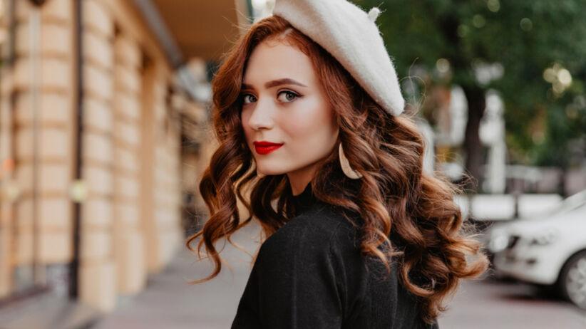 Piękna, rudowłosa kobieta z czerwonymi ustami idzie ulicą w płaszczu i białym berecie