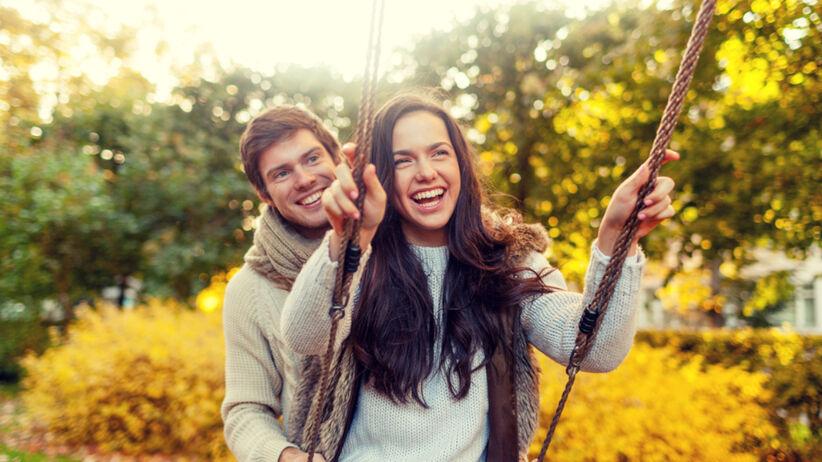 Szczęśliwa para w swetrach huśta się jesienią na huśtawce