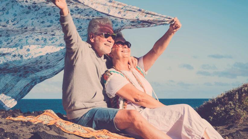 Starsza para szczęśliwa na plaży na wydmie nad brzegiem morza