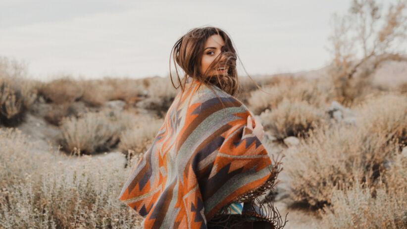 Tajemnicza dziewczyna zasłonięta długimi włosami w kolorowym ponczo jesienią