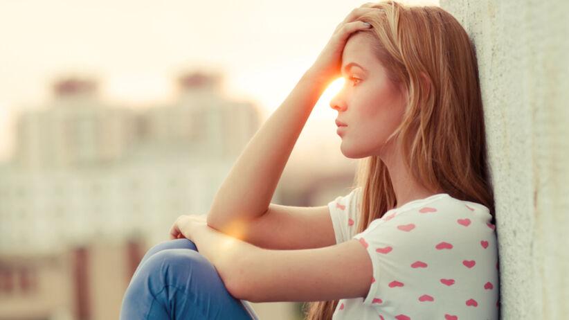 Młoda dziewczyna załamana złą decyzją na tle zachodzącego słońca