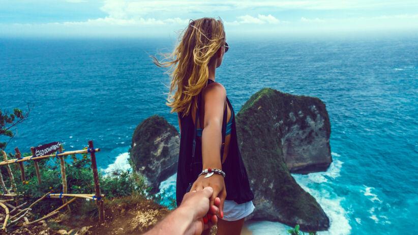 Młoda kobieta idzie po klifie, trzymając z tyłu za rękę swojego partnera i patrzy na morze