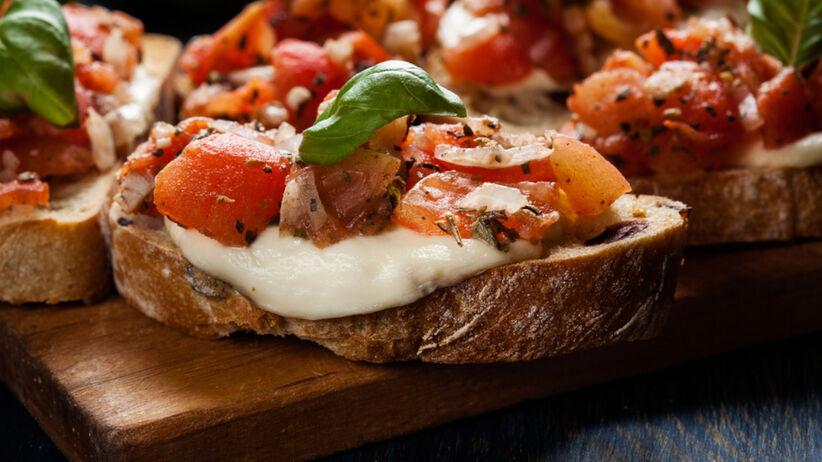 Bruschetta z bagietki z salsą pomidorową i mozzarellą leży na drewnianej desce