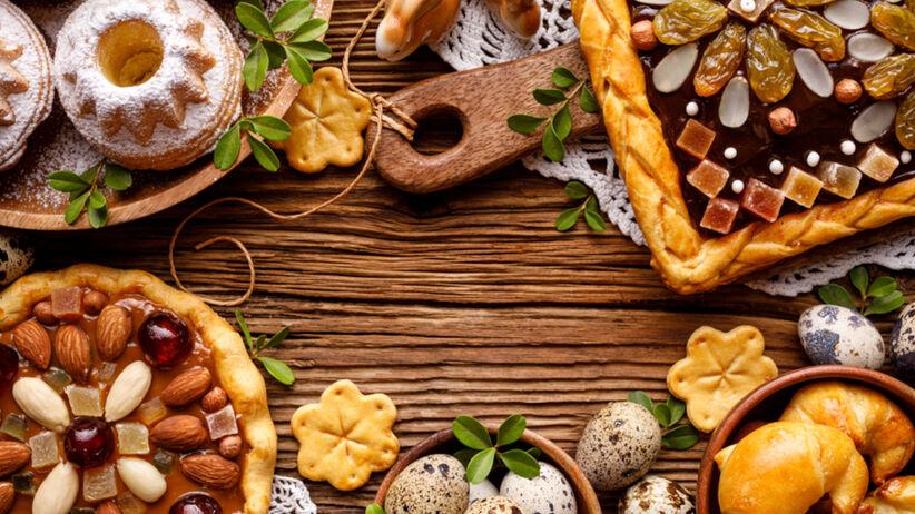 Ciasta na Wielkanoc stoją na drewnianym stole: babki wielkanocne, mazurek, rogaliki