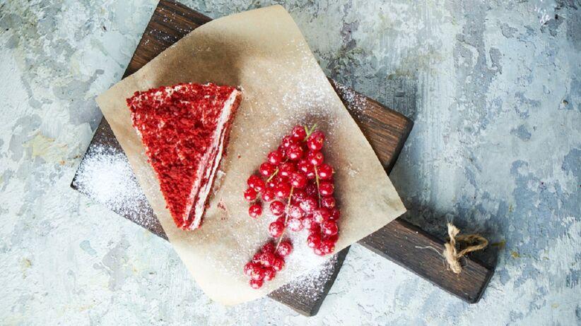 Na drewnianej desce do krojenia leży kawałek ciasta porzeczkowego.