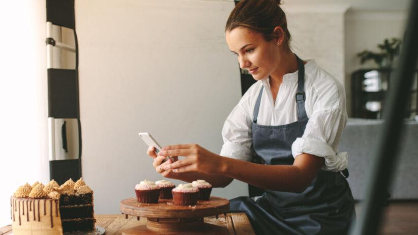 Młoda dziewczyna w fartuszku wypieka chleb i robi mu zdjęcie na Instagrama