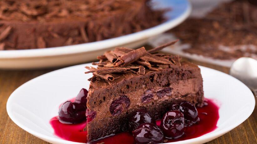 Na talerzu leży czekoladowe ciasto z wiśniami