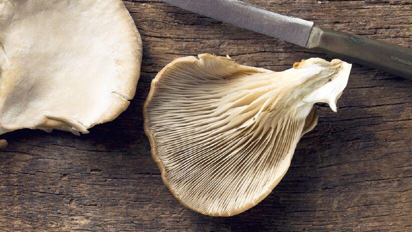 Na drewnianym blacie leżą boczniaki.