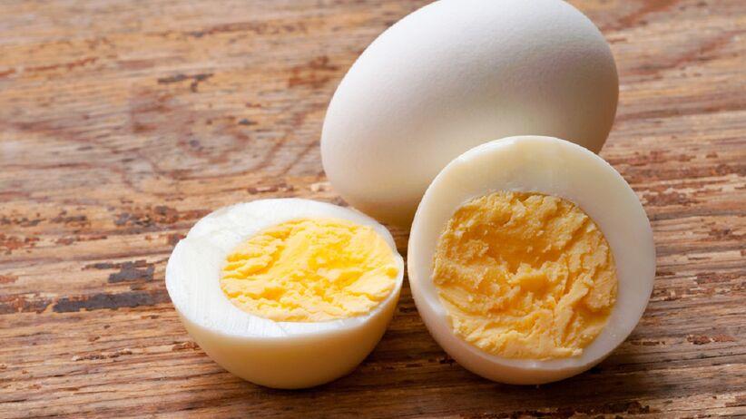 Na drewnianym blacie leżą jajka na twardo