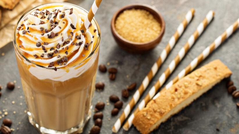 Kawa mrożona z karmelem i bitą śmietaną stoi na stole w szklance, ze słomką, a obok leżą słodycze