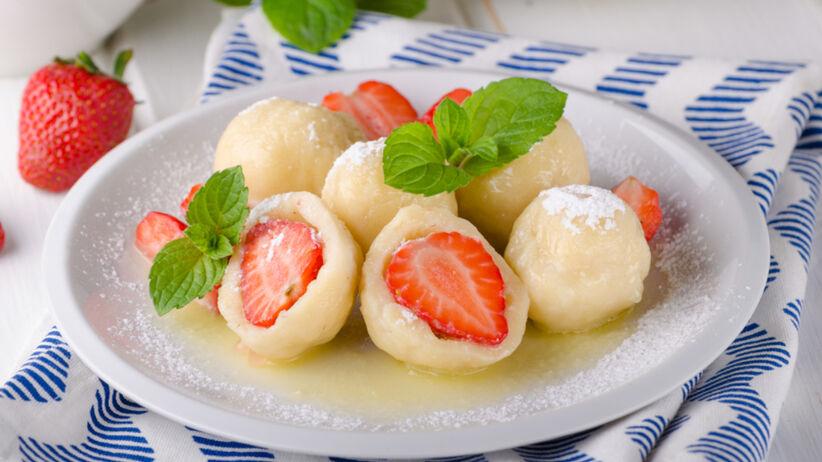 Knedle z truskawkami z okrasą na białym talerzu i posypane cukrem pudrem