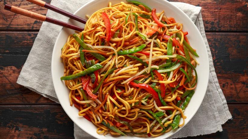 Makaron chow mein z warzywami w białym talerzy na drewnianym stole