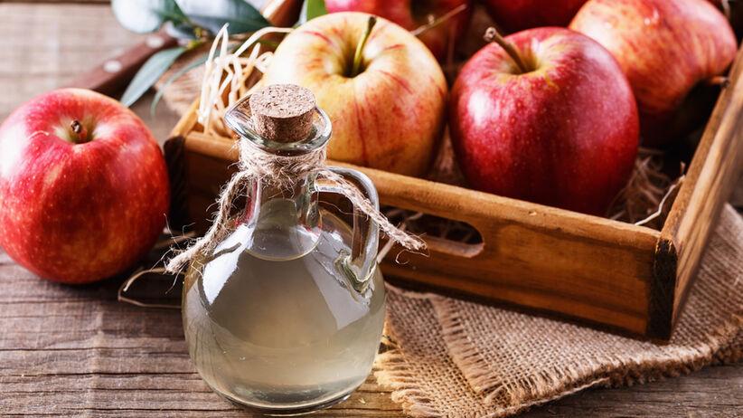 Ocet jabłkowy i jabłka w skrzynce w tle