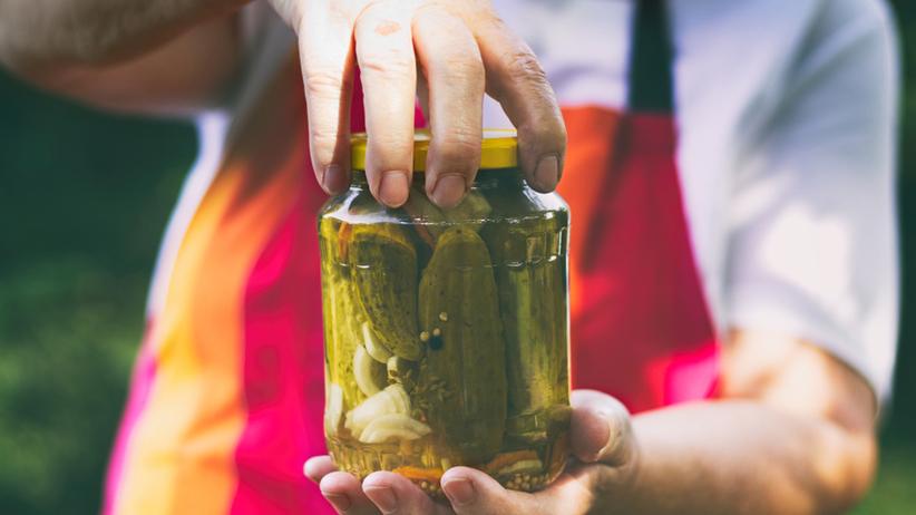Kucharz z kolorowym fartuszkiem trzyma słoik, w którym znajdują się ogórki konserwowe w occie z cebulą i gorczycą