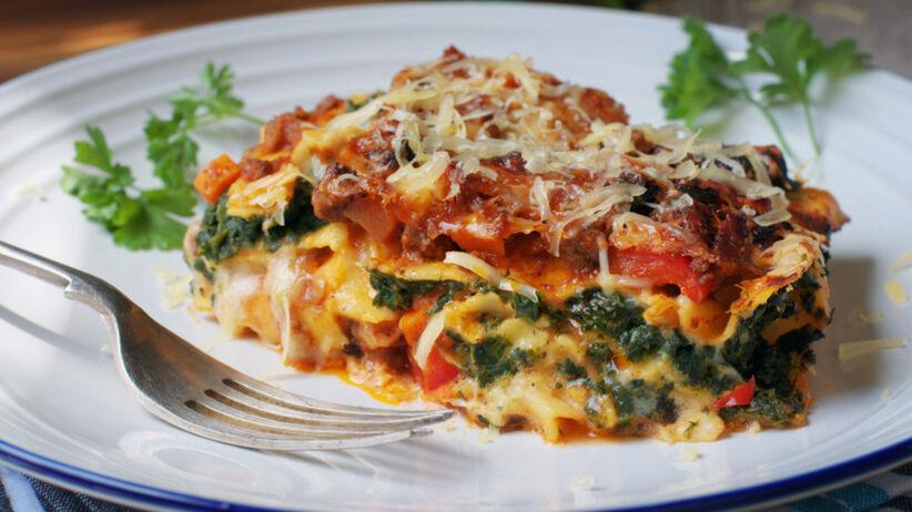 Lasagne ze szpinakiem i pomidorami na białym talerzu z natką pietruszki