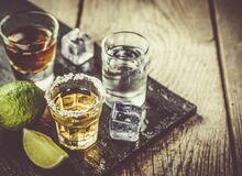 Na drewnianym blacie stoją kieliszki z alkoholem.