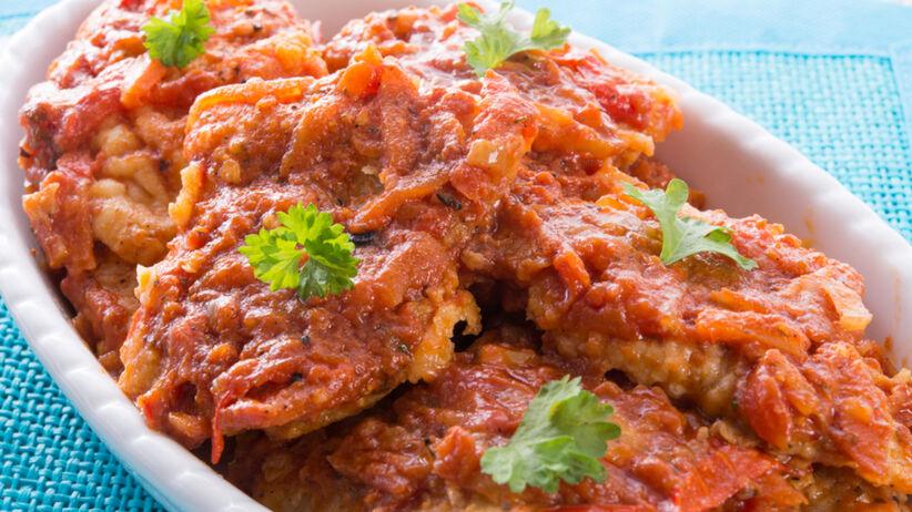 Ryba po grecku czyli ryba z warzywami w sosie pomidorowym w białym naczyniu żaroodpornym