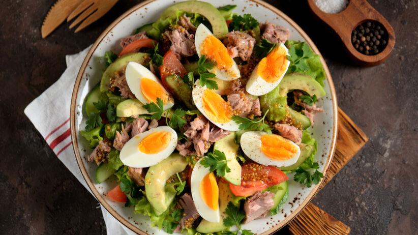 Sałatka z jajkiem, tuńczykiem, awokado na głębokim talerzu stoi na drewnianym stole