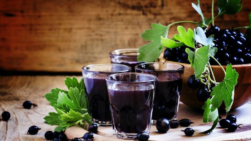 Na stole stoją szklanki z sokiem z czarnej porzeczki.