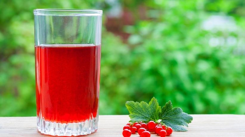 Na stole stoi szklanka z sokiem z czerwonej porzeczki